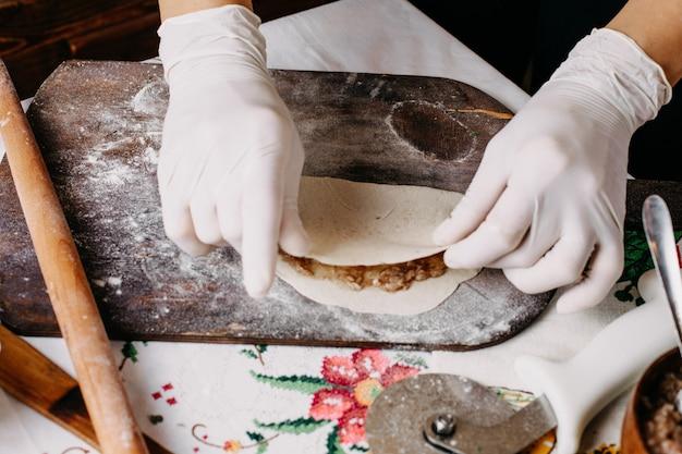Мясной кутаб в процессе приготовления теста на коричневом деревянном деревенском столе