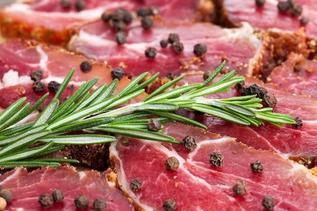 肉のマリネした豚肉、ローズマリーと一緒にテーブルに刻んだベーコンを添えた豚肉の製品