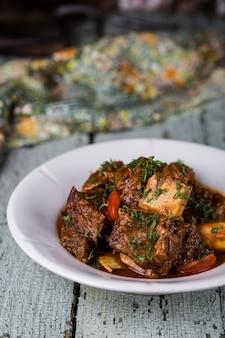 Мясные ребрышки на тарелке с томатным соусом