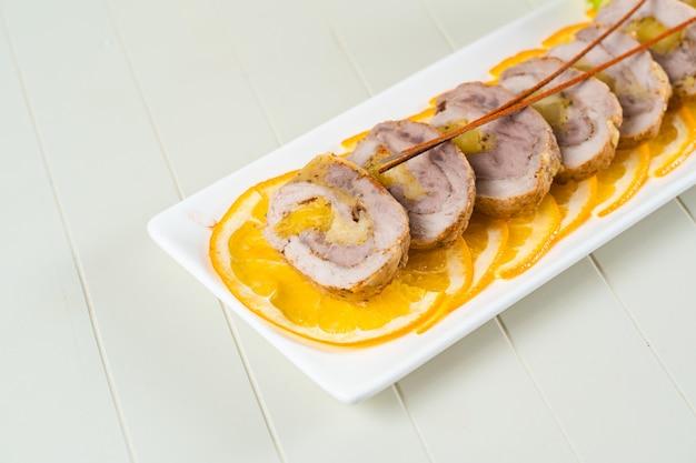 長方形の白いプレートのオレンジスライスに肉が転がります。スライスした豚肉の前菜。