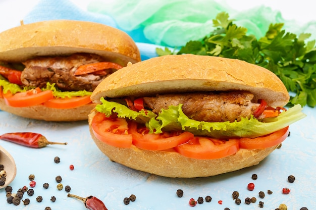 Meat rolls with vegetables in a bun with tomato and lettuce leaves.