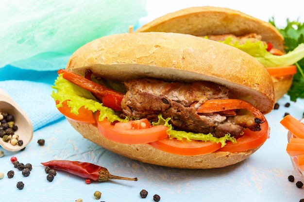 Meat rolls with vegetables in a bun with tomato and lettuce leaves
