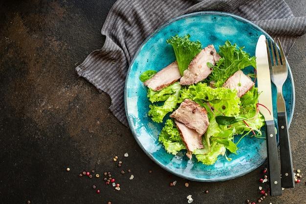 テーブルの上の肉サラダ野菜ジューシーな子牛のスライス
