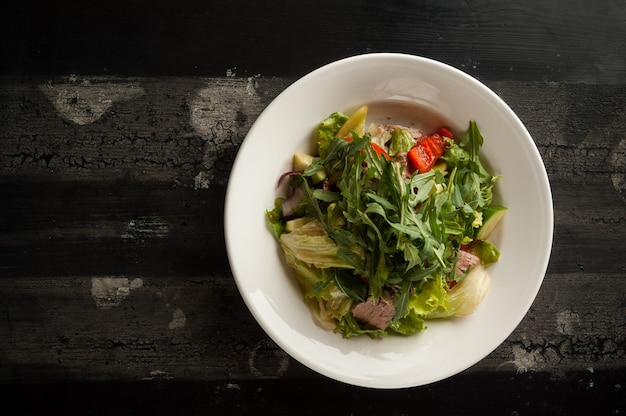 Meat salad in a white plate on a wooden old surface