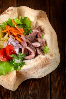 Meat salad with beef and fresh vegetables and lettuce in a plate-baked pita bread. copy space