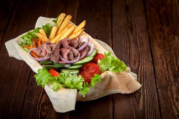 Meat salad with beef and fresh vegetables and lettuce in a plate-baked pita bread