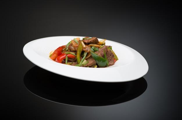 Мясной салат с болгарским перцем на черном фоне, изолированные