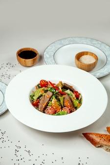 Мясной салат с овощами на столе