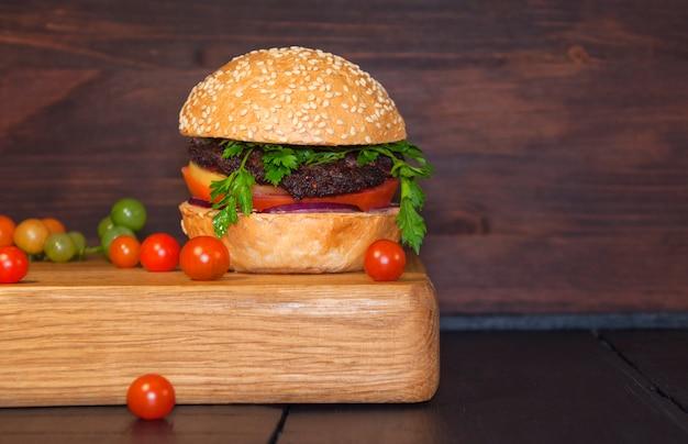 Meat sandwich sesame bun on a kitchen board