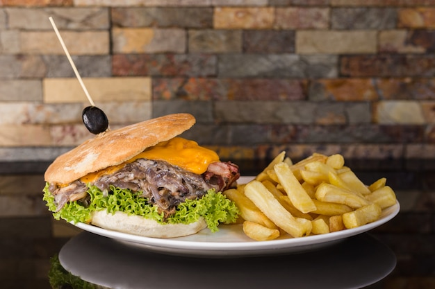 Meat sandwich with cheddar cheese, mushrooms, onion, lettuce, tomato, bacon and french fries