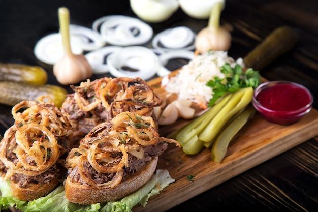 Мясной сэндвич с жареным луком, маринованными овощами и клюквенным соусом