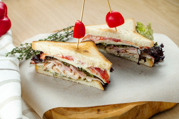Meat sandwiches on a cutting board. chicken, bacon and roast beef sandwiches. wooden background, close up
