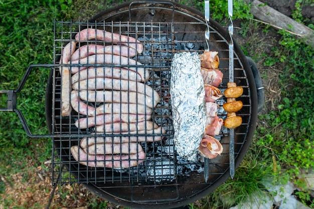Мясные колбаски, грибы в беконе и рыба в фольге готовятся на огне.