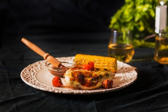 Meat served with cherry tomato and corn