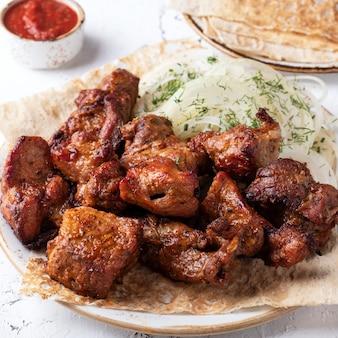 皿に肉のシシカバブ。サシュリクとレッドソース。閉じる