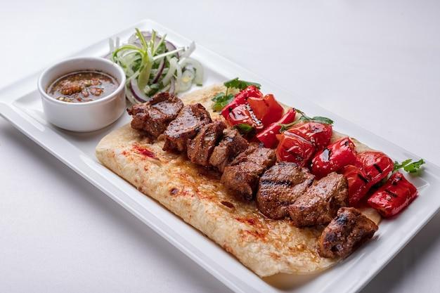 Мясной шашлык на лаваше с маринованным луковым соусом и запеченным болгарским перцем на белой тарелке на белой тарелке