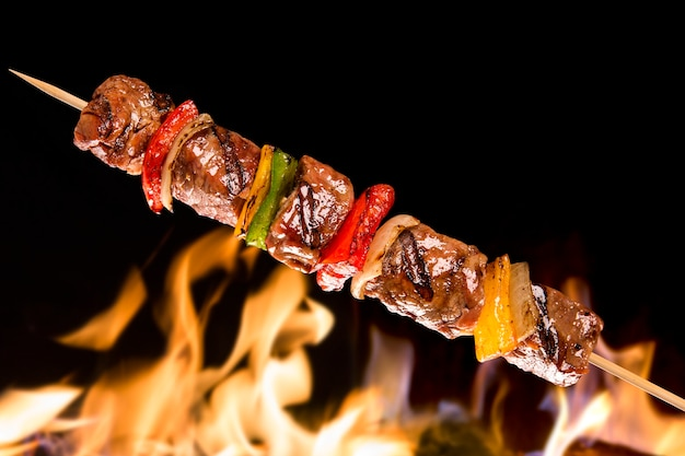 Meat skewer with vegetables over fire flames