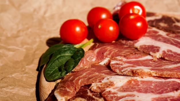 肉のスライスとチェリートマト。サンドイッチとブルスケッタの材料。おやつを調理します。ホウレンソウの葉。
