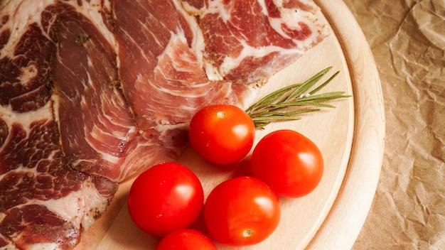 Ломтики мяса и помидоры черри. ингредиенты для бутерброда и брускетты. готовим закуски