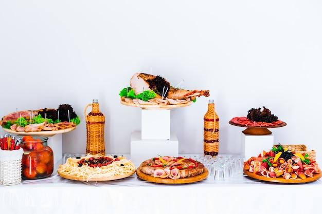 Кусочки мяса свинины на деревянных тарелках и свадебный прием напитка
