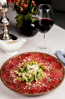 Meat slices with arugula and grated cheese served with glass of wine