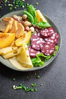 Мясные закуски тарелка колбаса сыр орехи персик фрукты тост хлеб копченая или сыровяленая закуска Premium Фотографии