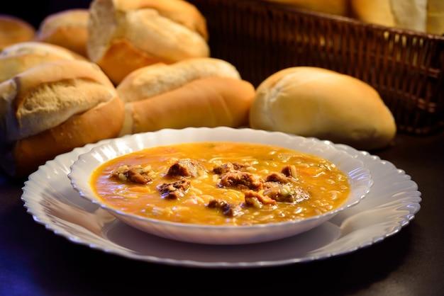 白い皿の上の肉汁と背景のパンブラジル北東部からの典型的な食べ物