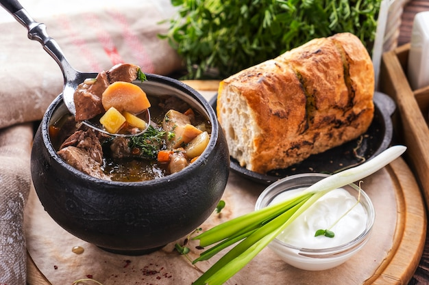 Meat soup with mushrooms and vegetables. meat soup in a pot with crispy bread