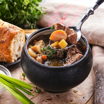 Meat soup with mushrooms and vegetables in a pot. macro view.