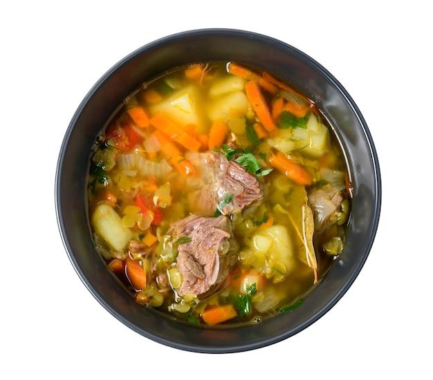 Мясной суп с овощами в черной миске, изолированной на белом. вид сверху