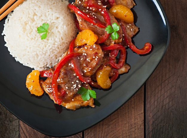 Meat in a spicy sauce, sweet pepper and tangerines with a garnish of boiled rice