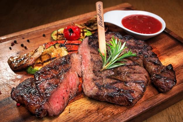 Мясной стейк на деревянной доске