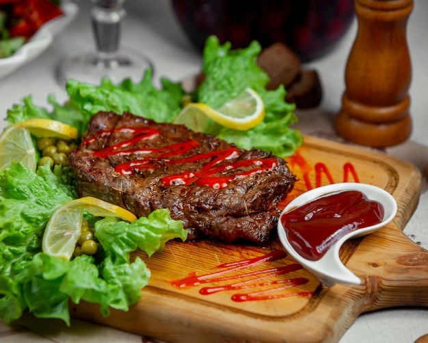 Meat steak served with ketchup