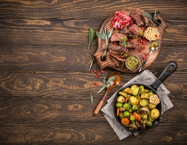 Meat steak with fried potatoes with vegetables and herbs on wooden cutting board