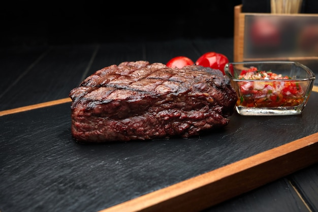Мясной стейк с овощами и соусом на деревянной доске с черным сланцем