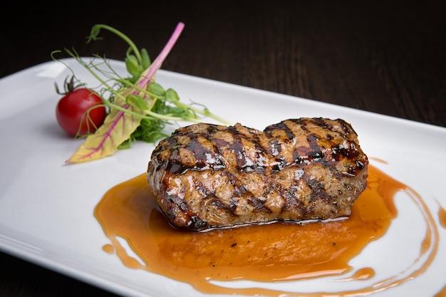 나무 보드에 하얀 접시에 야채 소스 데리야끼 고기 스테이크. 보기 상단