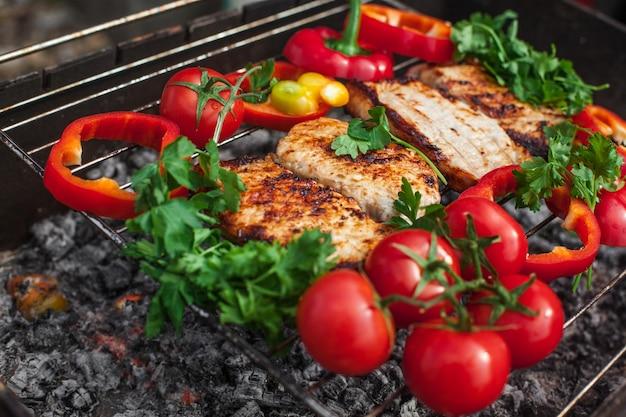 グリルでグリーン、トマト、コショウを添えたミートステーキ