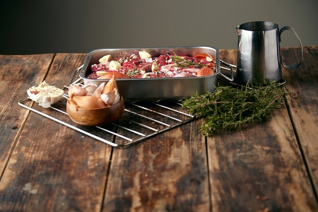 Meat in steel pan with spices around: garlic, rosemary, onions; ready to cook on wooden table