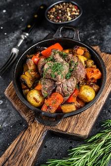 暗い素朴なまな板の調理鍋で肉のシチュー。黒の背景。上面図。