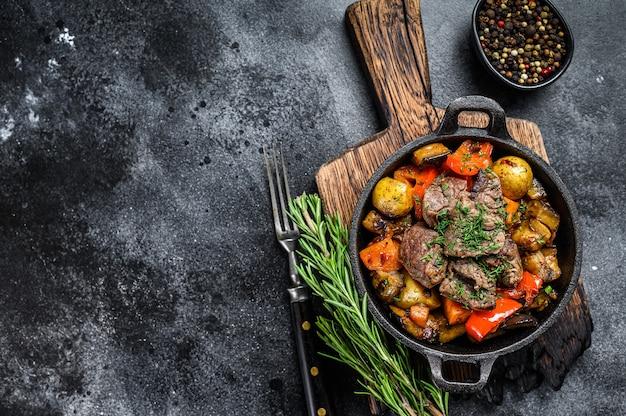 暗い素朴なまな板の調理鍋で肉のシチュー