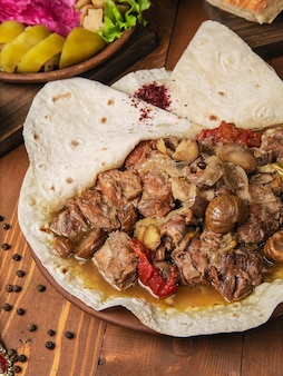 Meat stew, turshu govurma with onions, and chestnuts served in lavash