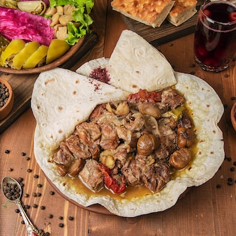 Meat stew, turshu govurma with onions, and chestnuts served in lavash.