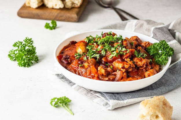 Meat stew with red beans, bell pepper and onion in tomato sauce in a white plate over light grey slate