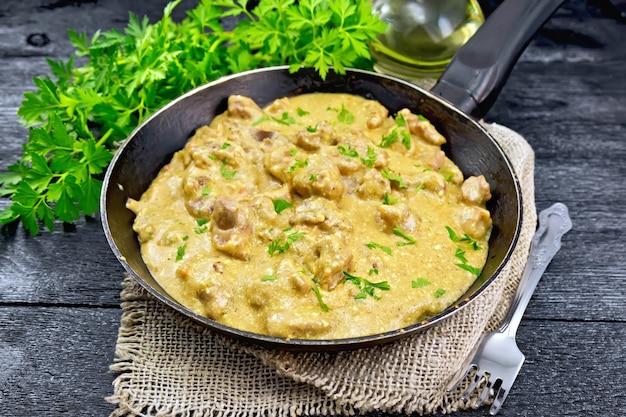 黄麻布の古いフライパンでクリームと煮込んだ肉、黒い木の板の背景にパセリ