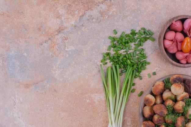 Мясные начинки подаются в деревянной чашке с зеленью и маринованными продуктами