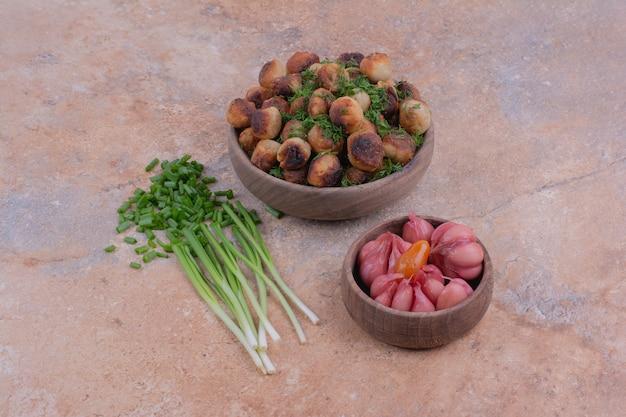 Ripieni di carne serviti in una tazza di legno con erbe e cibi marinati