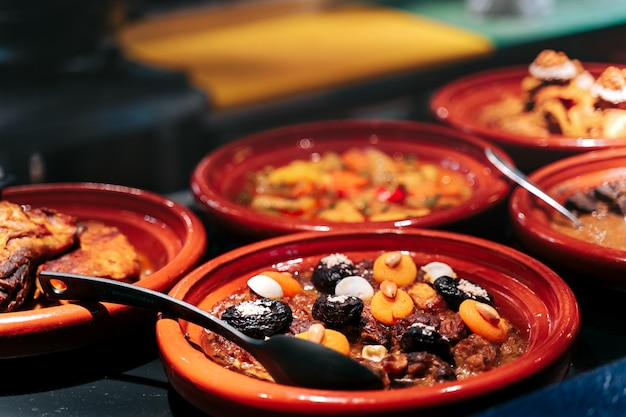 Meat tajine is a moroccan dish in sauce with dried fruits like prunes, apricot and toppings with almonds