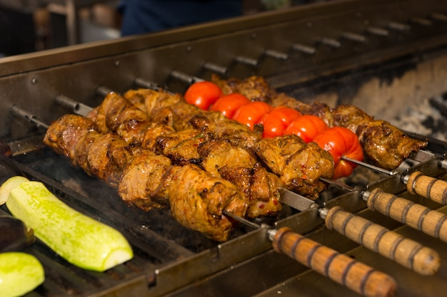 Meat and vegetable kebabs cooking on outdoor grill
