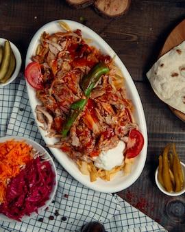 Мясо овощное рагу с помидорами и зеленым горячим перцем чили в белой тарелке.