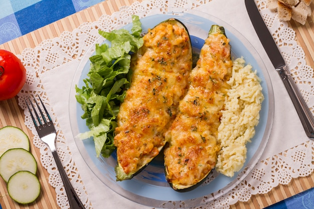 Meat and vegetables zucchini halves with rice and green salad.